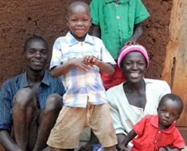 Denis has bount's disease and is standing with his family in Uganda.