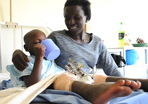 Denis lying on a hospital bed with his sister following his operation on his bowlegs at CBM supported hospital in Uganda.