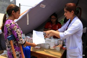 Receiving medicines at a relief camp organized by CBM partner HRDC (Hospital and Rehabilitation Centre for Disabled Children)