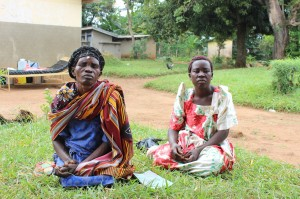 Joyce and her daughter sat outside the eye health centre in Uganda, pre-Trachoma Triasis operation, white tape identifies need for surgery, Namutumba distrcit, Busoga region