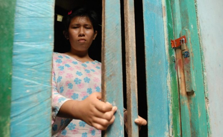Mental Health patient standing behind bars.