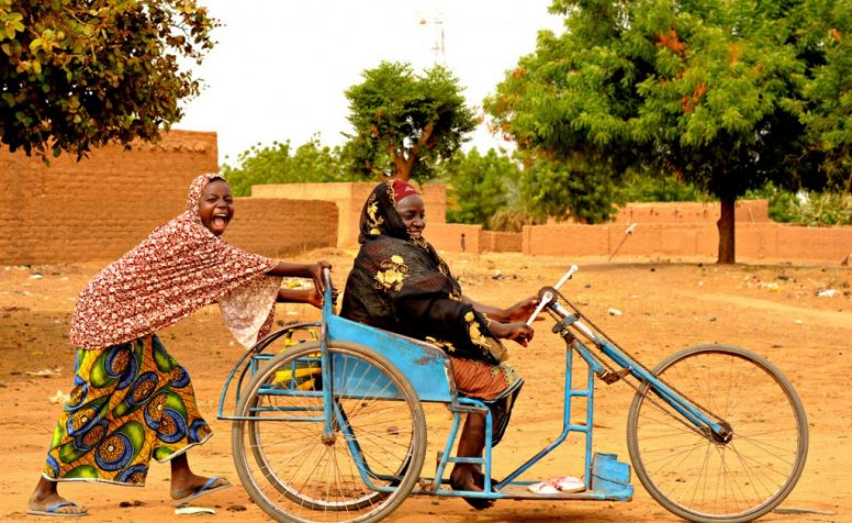 Jamila Amadou, who has untreated club feet, gets a push through the sand from a young woman in Kiota, Niger.