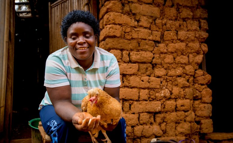 Mourine holds a chicken outside her home in Cameroon.