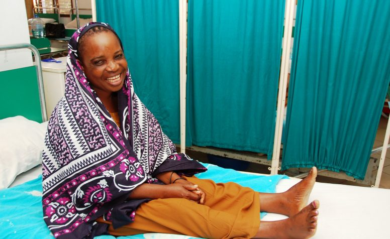 Dorotea from Tanzania sits on a bed after surgery for Fistula. CCBRT.