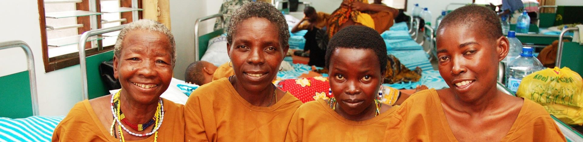 4 women sit on a hospital bed at CCBRT after fistula surgery.