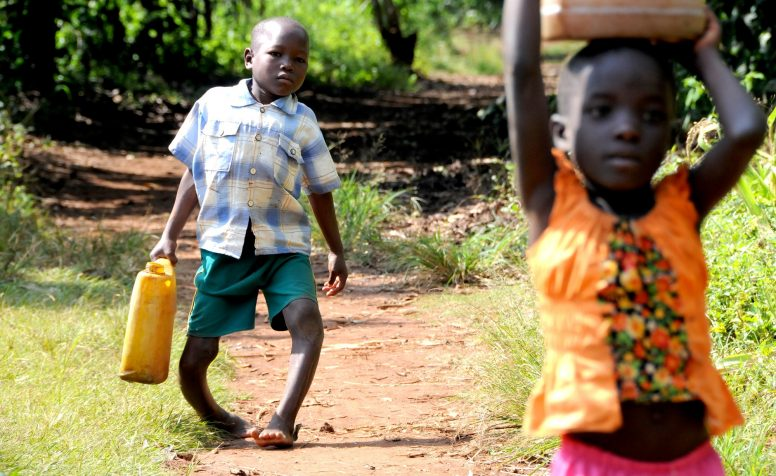Denis is carrying water from the water-hole back home  – together with his nieces Rita and Linda. Walking with bowed legs is burdensome – and causes Denis a lot of pain. .Please refer to related field reports for more information Denis (8 years old, born in June 2006) is a client of CoRSU Hospital in Uganda (P2429). During early childhood he developed severe bowlegs due to Blount´s desease. In CoRSU he will receive corrective surgery among other medical care and rehabilitation.