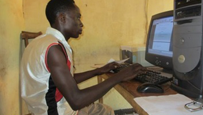 Eje sits at a computer that is in the shop that he owns thanks to ELIM in Nigeria.