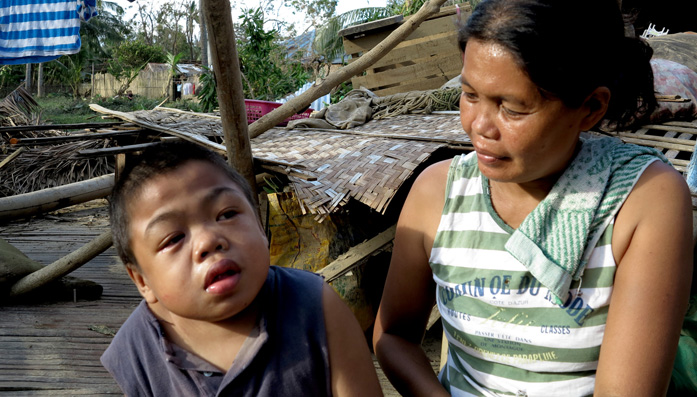 Flora sitting with one of her three children outside the rubble and mud that was once their home caused by Typhoon Haiyan in the Philippines.