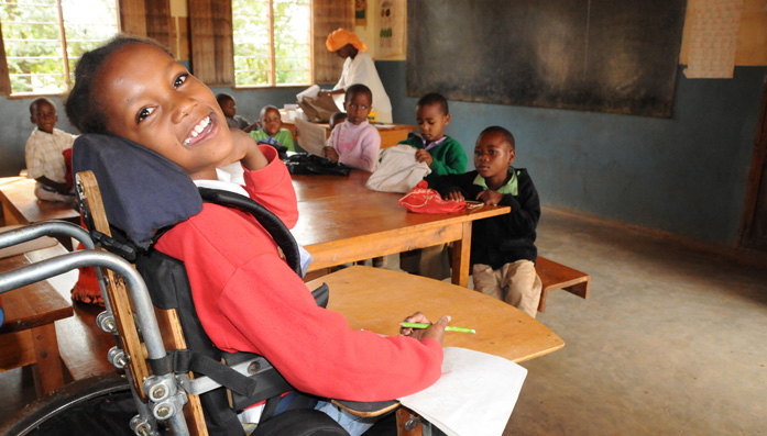 Grace in the classroom in her new wheelchair given to her by CBM-supported hospital in Tanzania.
