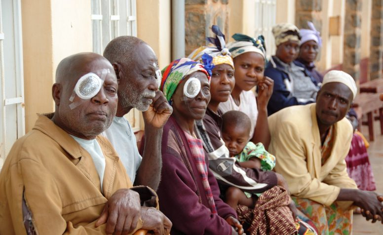 A line of children and adults with eye bandages on.