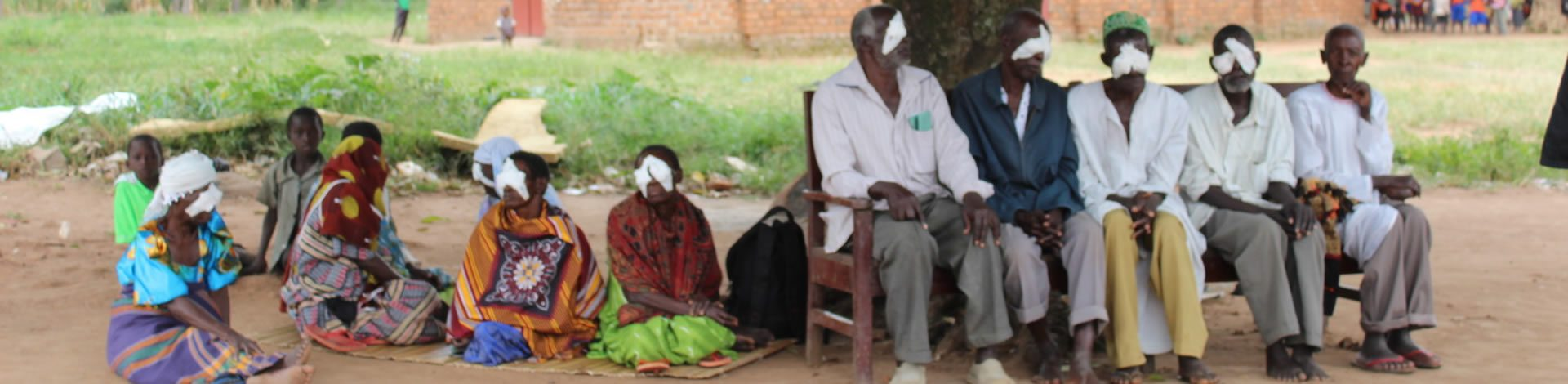 Joyce and other trachoma patients sit underneath a tree at Benedictine hospital with eye bandages on.