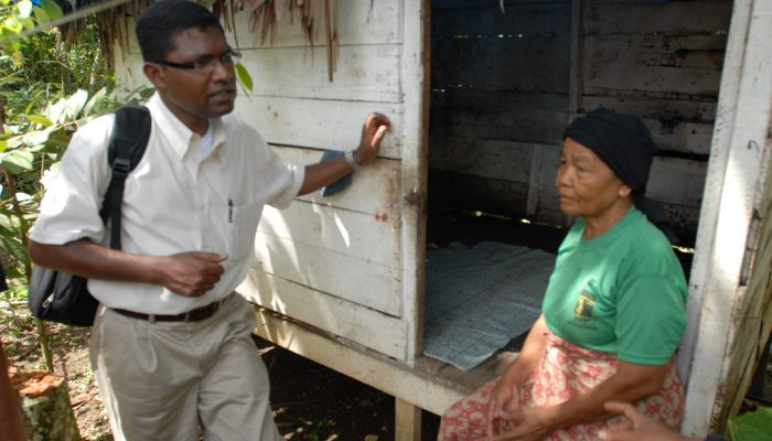 Dr. Andrew Mohanraj talking to Kandi about mental health support for her son Abdul Rani outside her house.