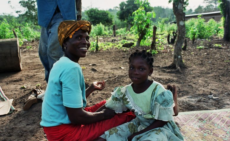 Sandrine sits on a blanket with her mother smiling, after her clubfoot surgery.