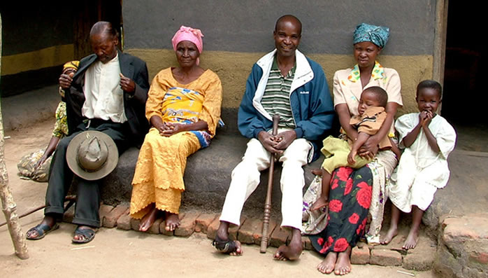 Bixon who has severely neglected clubfoot sits outside his house with his family