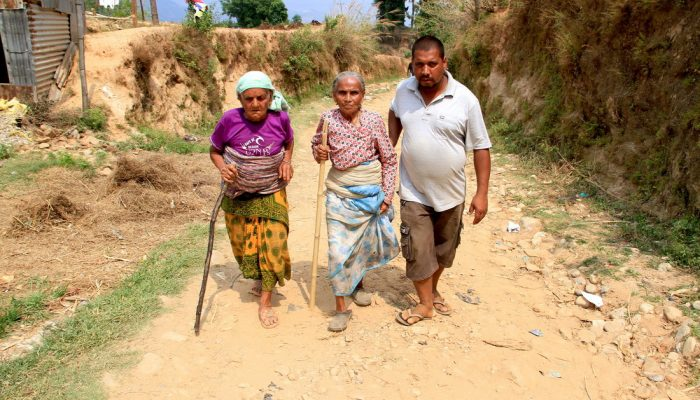 3 people walking to relief camp following Nepal earthquake.