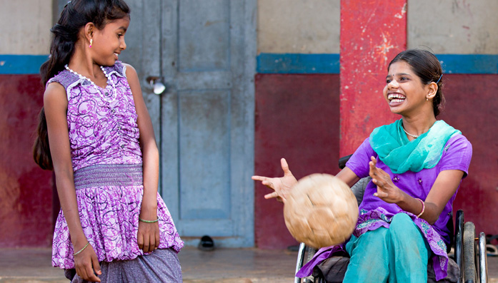 Shilpa in her wheelchair playing ball with her friend.