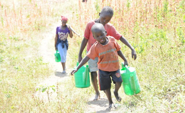 Augustine who has cataracts walks to the nearby Victoria Nile River to fetch water.