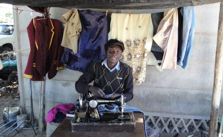 Henry working at his clothes making stall.
