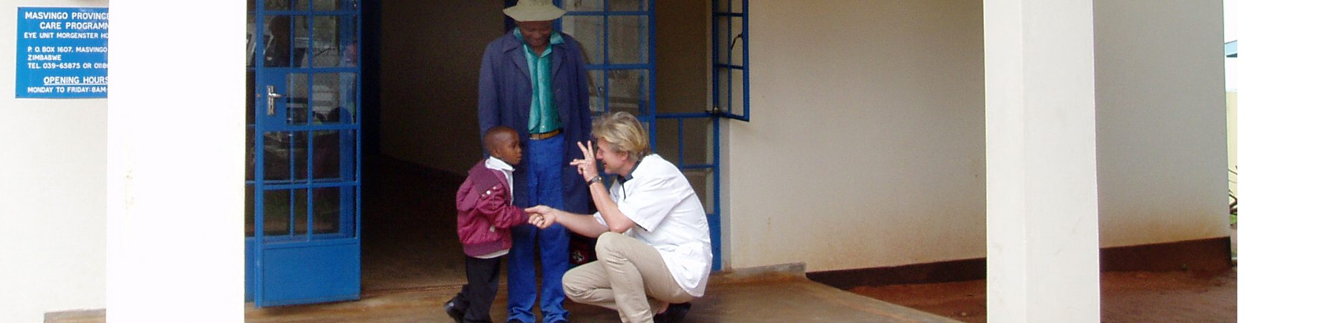 Doctor outside front of eye clinic testing young patient's eye sight in Zimbabwe.