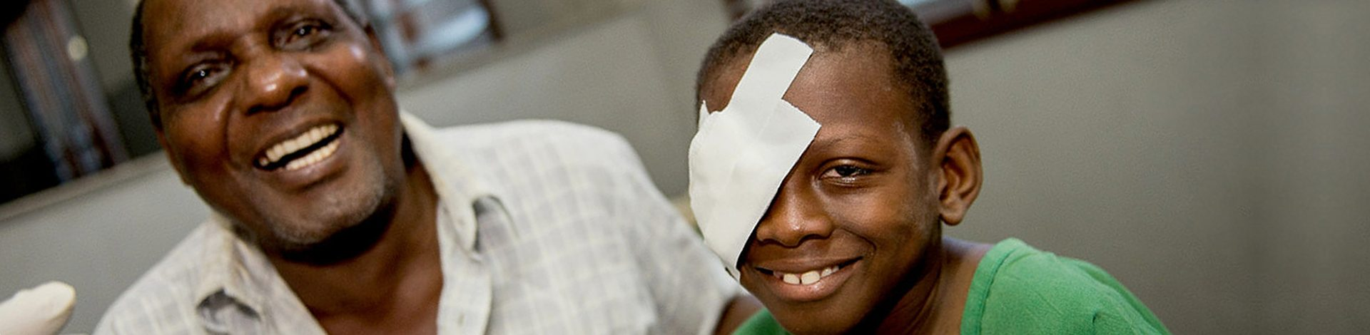 Omari and his father, Amiri can't stop smiling as a doctor comes and removes the bandages after cataract surgery.