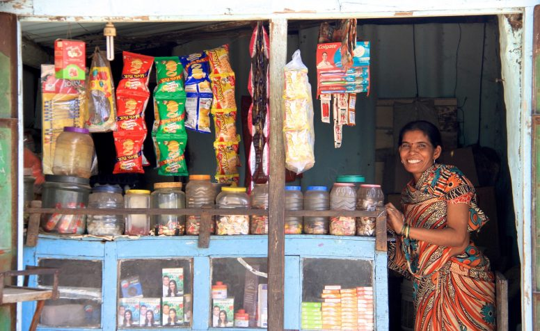 Usha stands inside her petty shop in Kothara village, India.