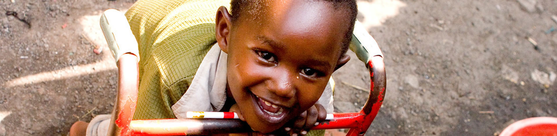 Muzuku has cerebral palsy and he is standing up with his red waggon.