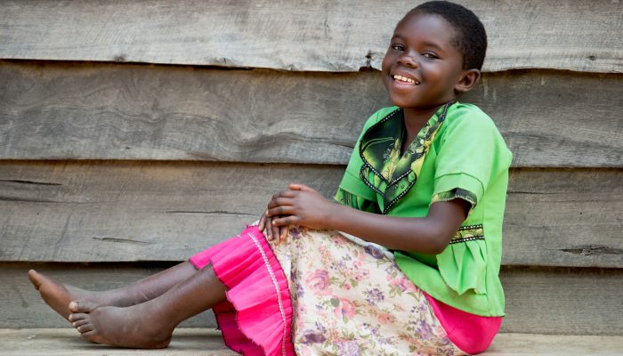 Rehema sits on the wall smiling after 3 months of clubfoot rehabilitation.
