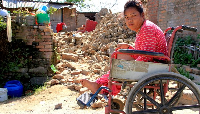 Purna Maya sitting in her wheelchair outside her destroyed house.