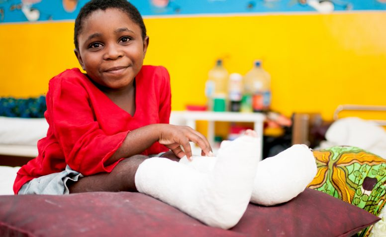 Zawad smiles after clubfoot surgery on hospital bed.