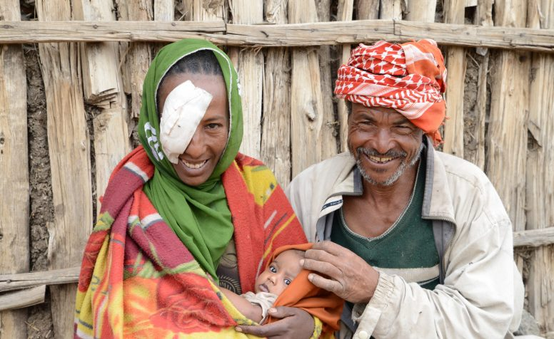 Smiling Serkie with her husband and child wearing an eye-patch after surgery for trachoma.