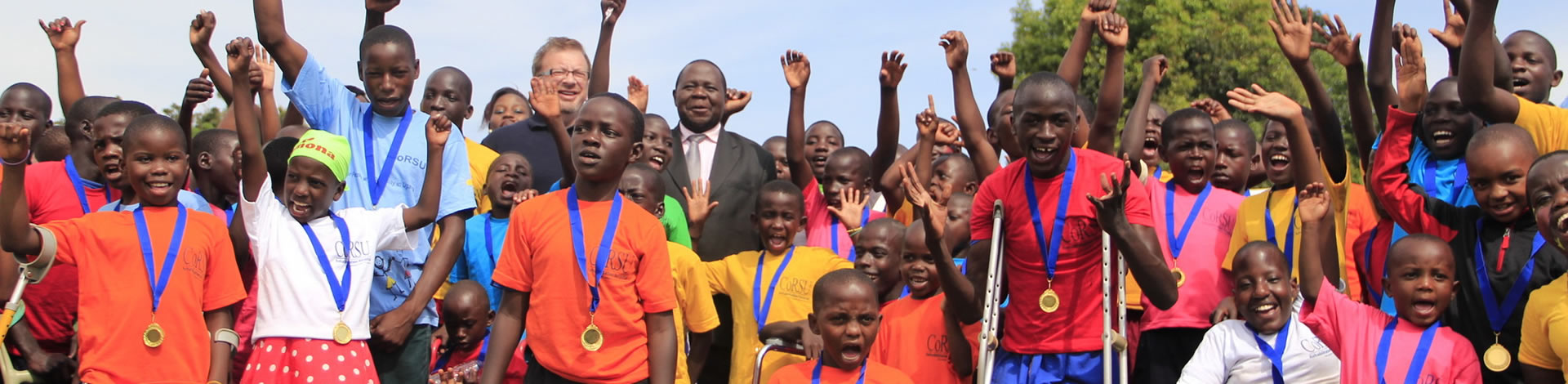 Children with disabilities cheering and wearing medals after disability sports event at CORSU hospital in Uganda.