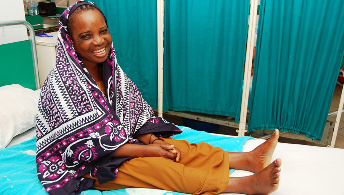 Dorotea from Tanzania sits on a bed after surgery for Fistula.