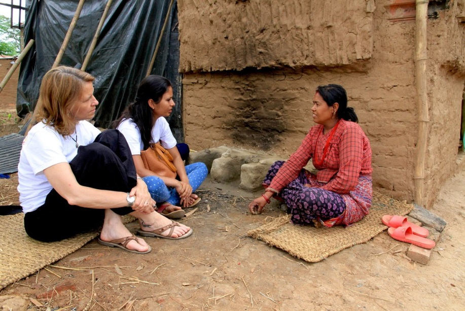 Kirsty Smith sitting on a woven matt talking to women affected by Nepal earthquake.