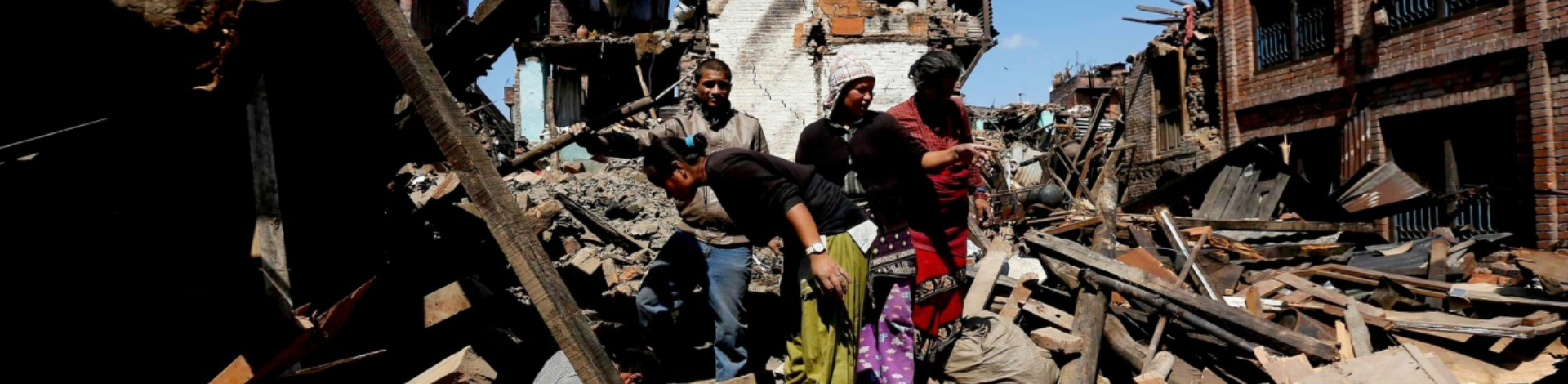 Women and men standing on top of rubble where kathamandu once stood, following Nepal earthquake in 2015.