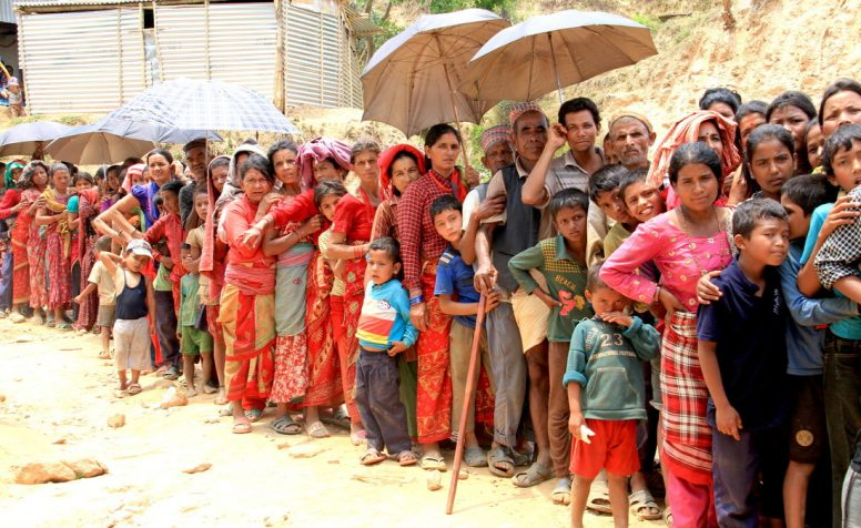 Que of women and men waiting for emergncy aid at a CBM relief camp.