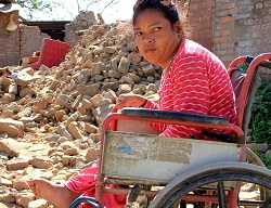 Purna Maya in her wheelchair in front of her ruined house.