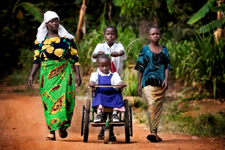 Young girl being pushed by her family in her wheelchair to school.