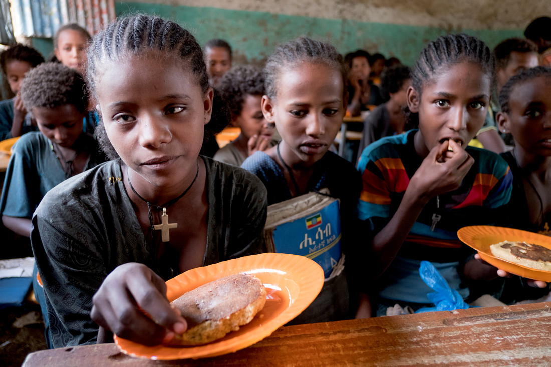 Children with bread provided by the school feeding programme