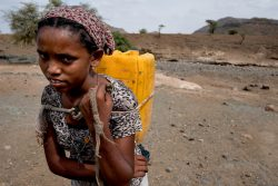 Meseret, 16, carrying water container through dry landscape