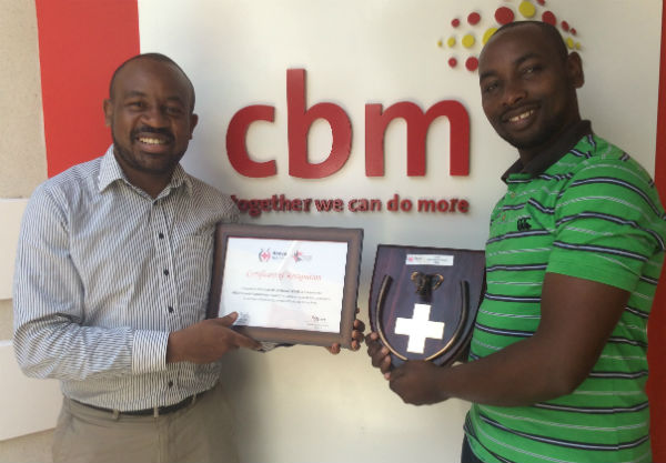 Eric Limiri (left) handing over the Award to Mr. Amos Mutiga CBM Kenya Executive Director