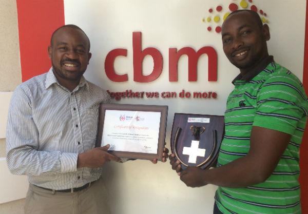 Eric Limiri (left) handing over the Award to Mr. Amos Mutiga CBM Kenya Executive Director