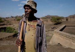 Berara, a farmer, stands next to the empty dam