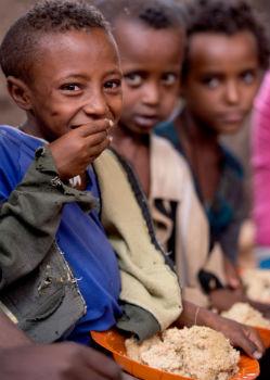 Primary school children eating porridge