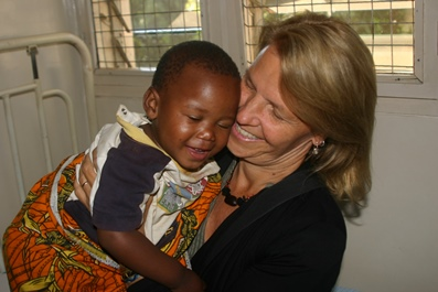 Kirsty Smith CEO hugging child before cataract surgery at KCMC in Tanzania.