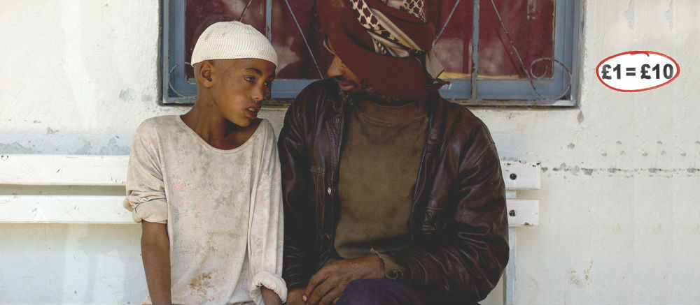 Nasire, who has trachoma, sits with his father - your gift multiplies £1=£10