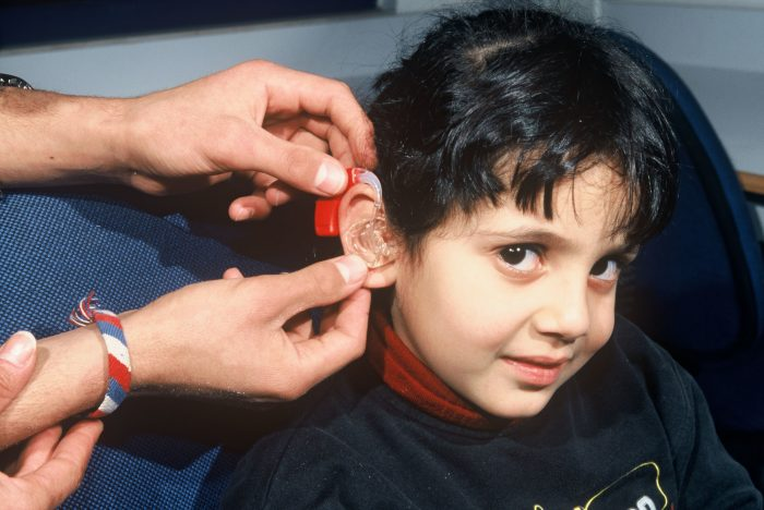 Six-year-old Asiel having a hearing aid fitted by Yoakeem Habash in the ear mould lab. The sixteen years old deaf Yoakeem is attending school in the HLID, where he is also having vocational training. The Holy Land Institute for the Deaf (HLID) in Salt/Jordan is a rehabilitation centre for hearing impaired children and young people. The center is consisting of a school including kindergarten, a department for vocational training, a section for hearing aids including a small audiology clinic (H.E.A.R.), an outreach programme and a training centre for teachers (S.T.R.I.D.E.). - Local partner: The Episcopal Church in Jerusalem and the Middle East - P. 1135 -  Picture was taken during a research trip to Jordan from 13 - 18 January 2003.  - For further information see travel report (PDF format): JOR-03-002.pdf