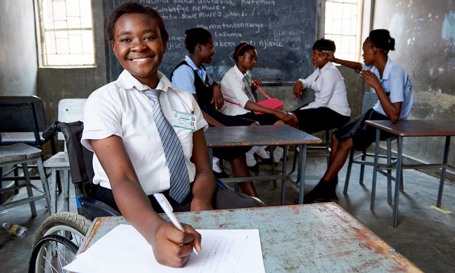 Abigail from Zambia sits at a desk in her classroom in a wheelchair
