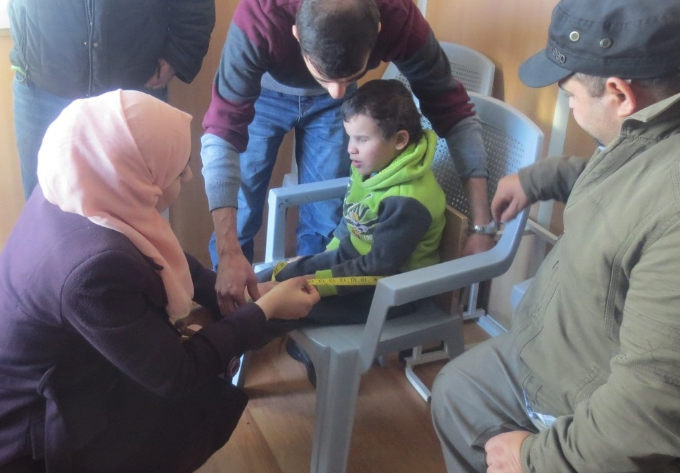 Al Hussein Society staff measuring Syrian child for mobility device in Azraq refugee camp, Jordan .