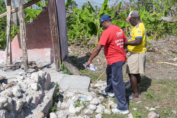 Hurricane Matthew - Haiti - October 2016. Communications visit December 2016. Rene showing CBM Community Worker Homer Auguste what is left of his house in Torbeck, Haiti after Hurricane Matthew made landfall. Read full story in CBM Media Database.