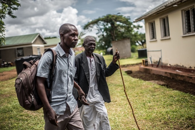 James Murambwe leads Nasani from the camp vehicle to the health centre for surgery. After the procedure, he will be able to see to move around independently.